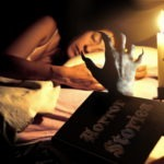 devil hand coming out from horror book on Halloween night