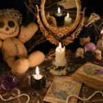 Magic ritual with voodoo doll, mirror and tarot cards
