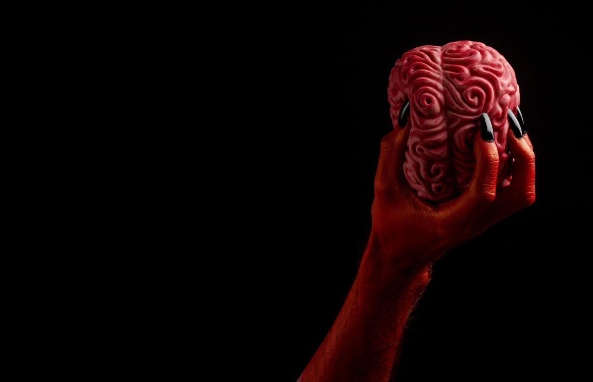 Red devil hand holding a human brain. Halloween concept
