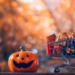Halloween festival shopping concept. Halloween pumpkins with shopping cart on wood background.